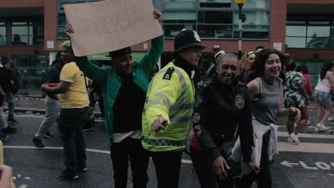 Policeman dances with participants at UK carnival