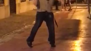 Music guy with black headphones on running around in circles in the street dancing