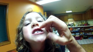 Adorable little girl asks for help with loose tooth - Video