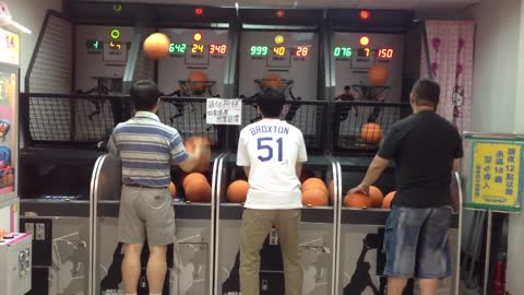 Man Shoots Hoops At The Arcade With Both Hands