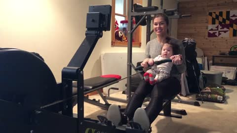 Baby girl and mom workout together on rowing machine