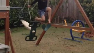 Little girl on green backyard kid swing falls off