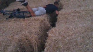 Guy rides bike on hay and falls face first - Video