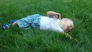 the child enjoys the thick grass. - Video
