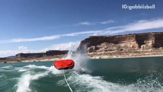 Slow motion three people fall off of red black raft lake - Video