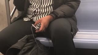 Woman in black and white shirt sings out loud on subway