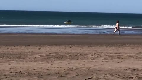 Surfer in the distance does push ups on his surfboard while on the water