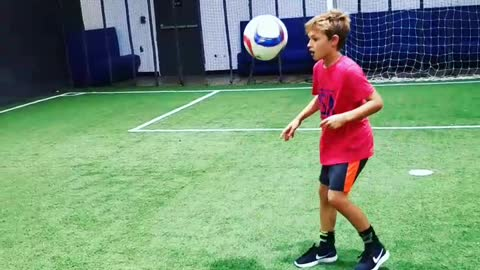 Young soccer star makes trick shot off wall