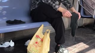 Man rubs bare foot on subway train - Video