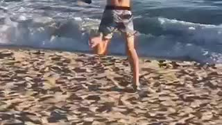 Guy blue shorts running funny on beach toward water