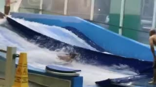 Yellow boogie board kid faceplants on wave machine indoors - Video
