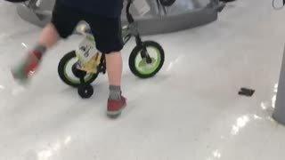 Kid rides a small green bike and falls back - Video