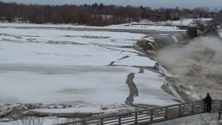 Warming river breaks apart ice, sends it over waterfall edge - Video