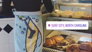 Guy in wetsuit and blue socks at a cafe  - Video