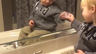 Little Boy Clinks Glasses With His Reflection - Video
