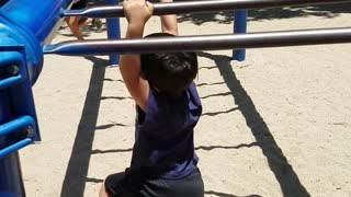 Little kid black shirt monkey bars face plants into sand woodchips