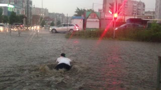 Man Swims Across a Flooded Street
