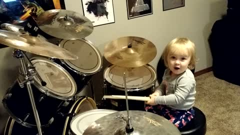 Little girl adorably tries to play the drums