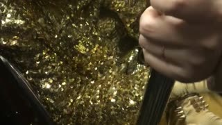 Person sprinkle sparkle all gold subway sitting - Video