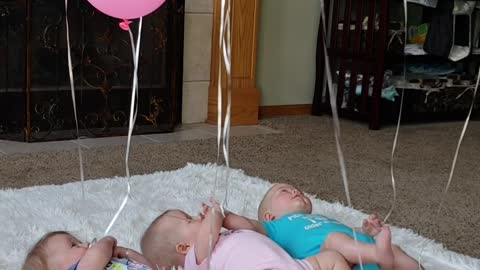 Triplets Playing with Balloons