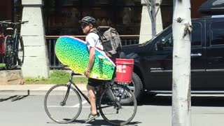 Guy riding bike holding colorful blue yellow surfboard