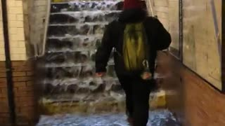 Person in red beanie walks up stairs with water running down