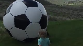 Dad kicks huge soccer ball and knocks baby out! - Video