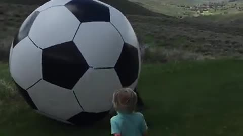 Dad kicks huge soccer ball and knocks baby out!