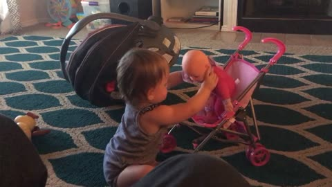 Little toddler plays with her doll