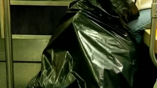 Person white headphones looking through big black trash bag - Video