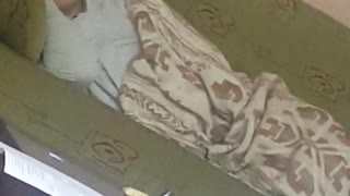 Guy in blue shirt laying on green couch gets woken up by bottle  - Video