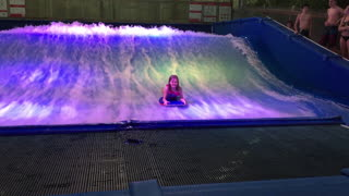 Young girl braves surf simulator, wipes out instantly!