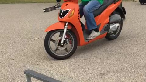 Guy in green rides orange bike into fence
