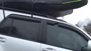 Silver car drives with surfboard on top of car - Video