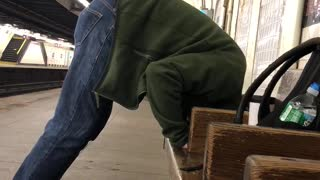 Guy blue jeans green jacket head in wooden seats standing subway - Video