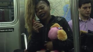 Girl subway holding pink stuffed animal spinning hair singing