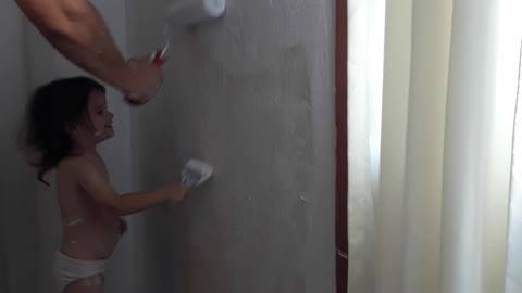 2 year old helps her dad painting the house