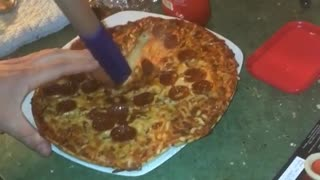 Guy cutting pizza with swiffer handle bar  - Video
