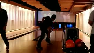 Guy falls in bowling alley after letting go of ball - Video