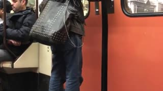 Woman with black cat on her shoulder can't wait to get out of subway train doors