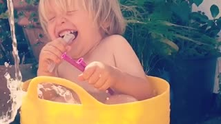 Little boy loves being watered in bucket  - Video