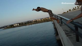 Shirtless guy front flip off bridge slaps back - Video