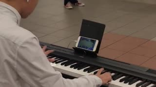 Man playing piano while playing games on phone - Video