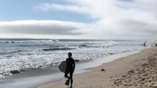 Boogie boarder walks down beach with flipper feet - Video
