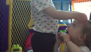 Baby girl dances and drums on her twin sister's head - Video