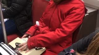 Woman uses typewriter on a subway train