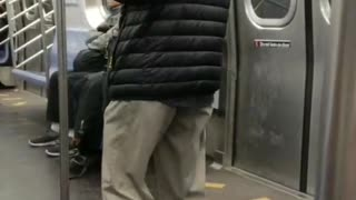 Old man hat plays wooden flute on subway