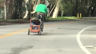 Green guy rides bicycle with wagon attached behind him