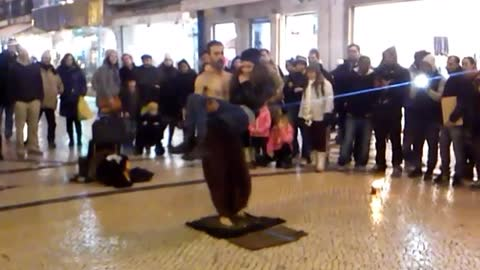 Street performer walks over broken glass