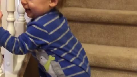 Twin baby extremely amused by brother on stairs